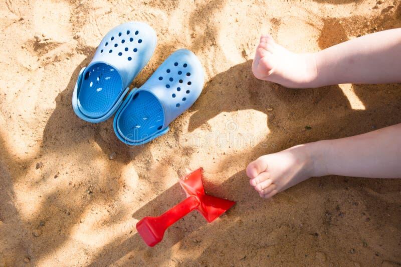 baby& x27; s lägger benen på ryggen i strandsanden, blått bläddrar misslyckanden och en leksakskyffel, lek i sandlådan royaltyfria foton