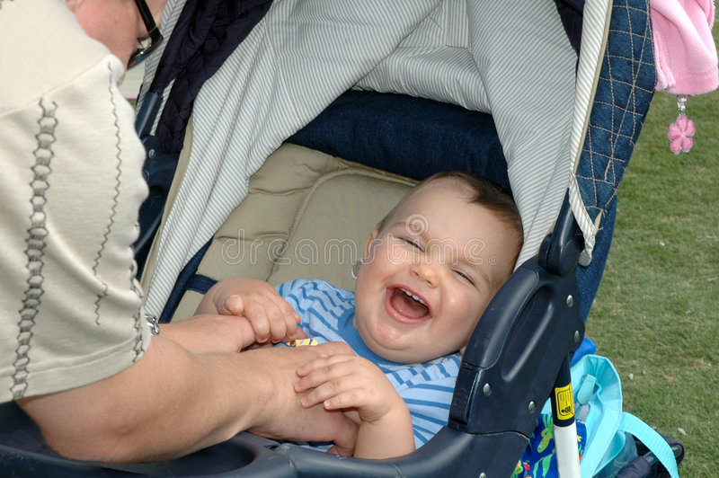 A Baby's Laugh. Little baby boy sitting in stroller laughing at being tickled royalty free stock image