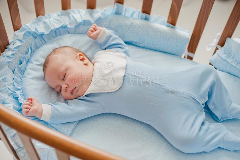 Baby`s restful sleep. Newborn baby in a wooden crib. The baby sleeps in the bedside cradle. royalty free stock photography