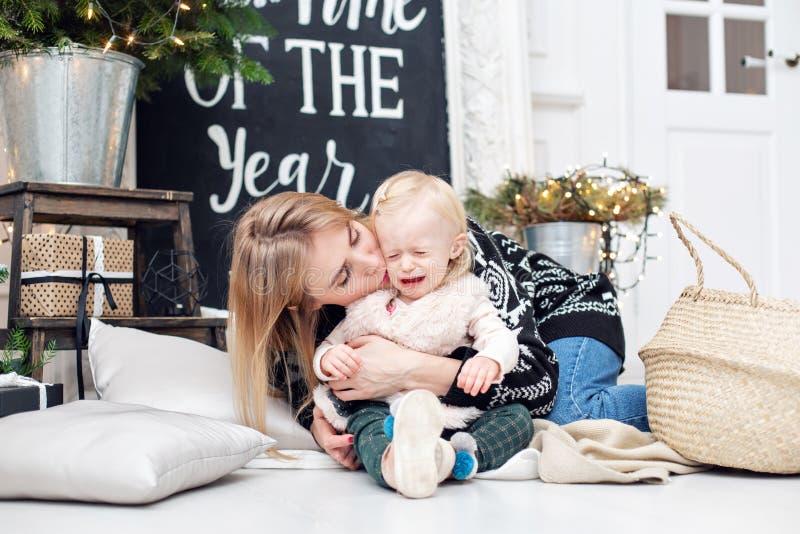 Baby ` s Schreien Nette Mutter umfasst ihre nette Tochter Elternteil und kleines Kind, die Spaß nahe Weihnachtsbaum zuhause haben lizenzfreie stockfotos