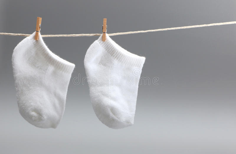 Baby's Socks. Pair of socks hanging on the clothes line royalty free stock image