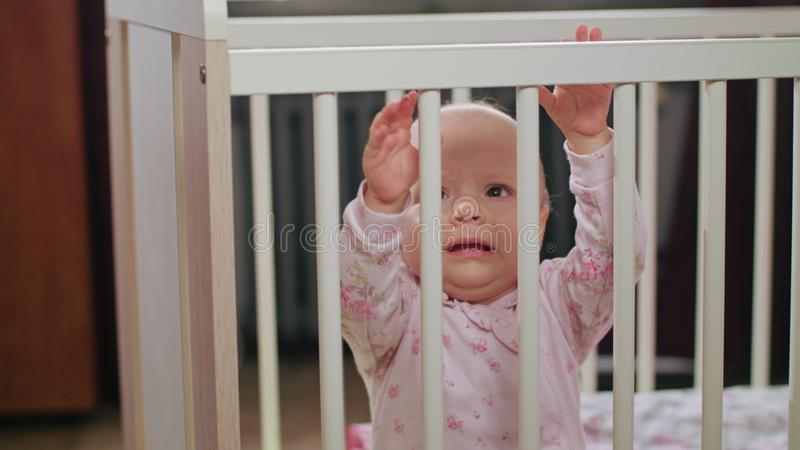 Baby Standing in a Crib at Home. Crying. Baby`s standing in a white crib at home and crying. Medium shot royalty free stock photo