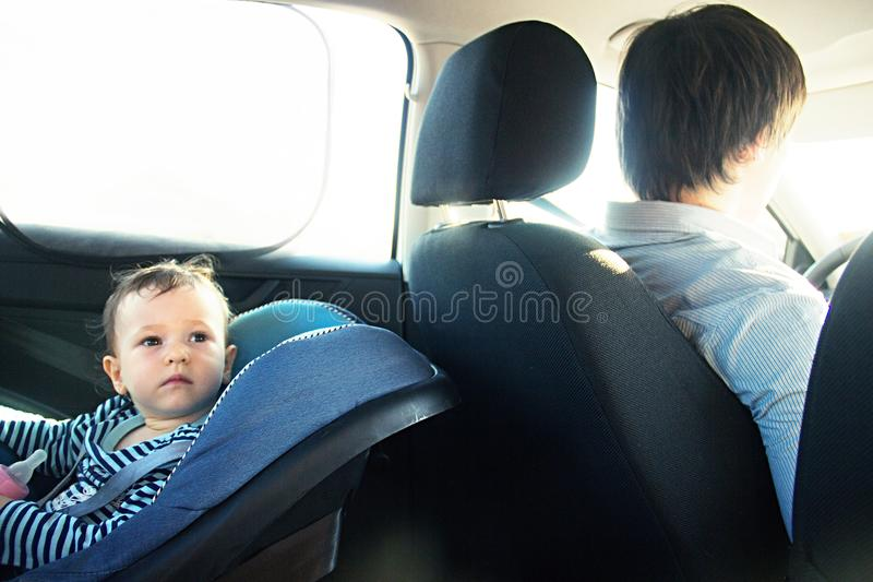 Baby in a safety car seat. security. one year old child girl in blue wear sit on auto cradle. Rules for the Safe Transport of Chil. Baby smile in a safety car royalty free stock photo