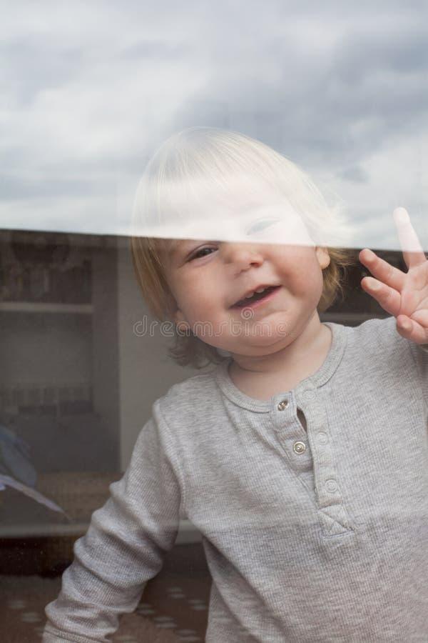 Baby saluting through glass stock photos