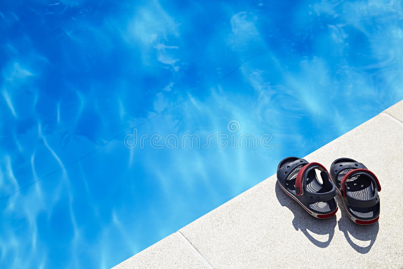 Baby sandals at the swimming pool. Pair of baby sandals at the swimming pool at sunny day. Copy space royalty free stock images