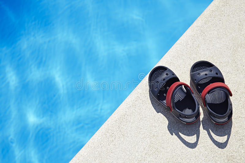 Baby sandals at the swimming pool. Pair of baby sandals at the swimming pool at sunny day. Copy space stock photos