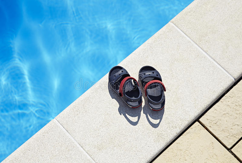 Baby sandals at the swimming pool. Pair of baby sandals at the swimming pool at sunny day. Copy space stock images