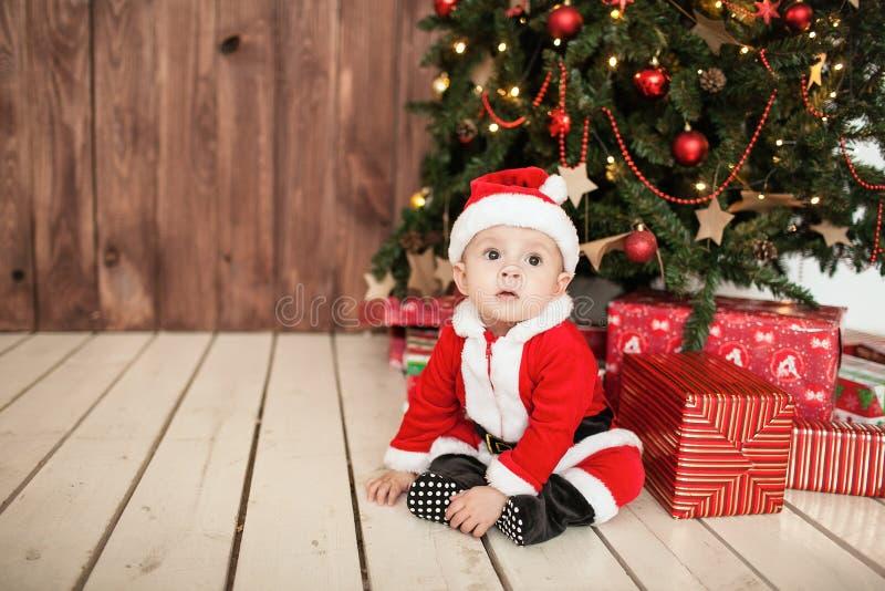 Baby in Sankt-Klage mit Geschenken nähern sich Weihnachtsbaum stockfotografie