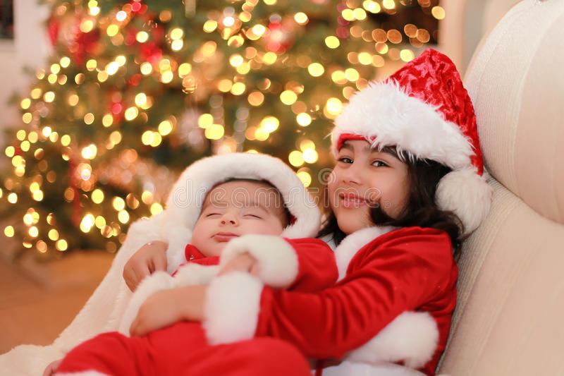Baby santa. Girl holding her little baby brother, both wearing christmas clothes royalty free stock photos