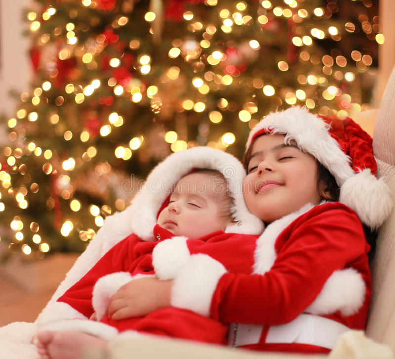 Baby santa. Girl holding her little baby brother, both wearing christmas clothes royalty free stock images