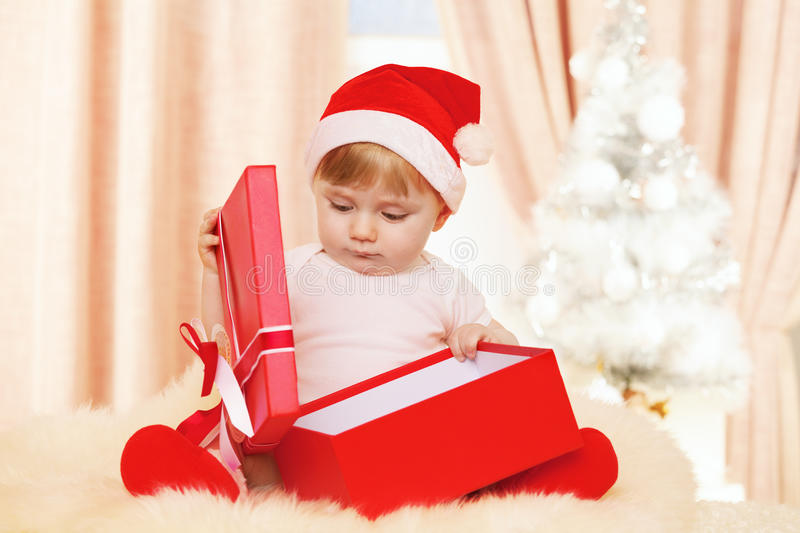 Baby santa with big red gift box stock images