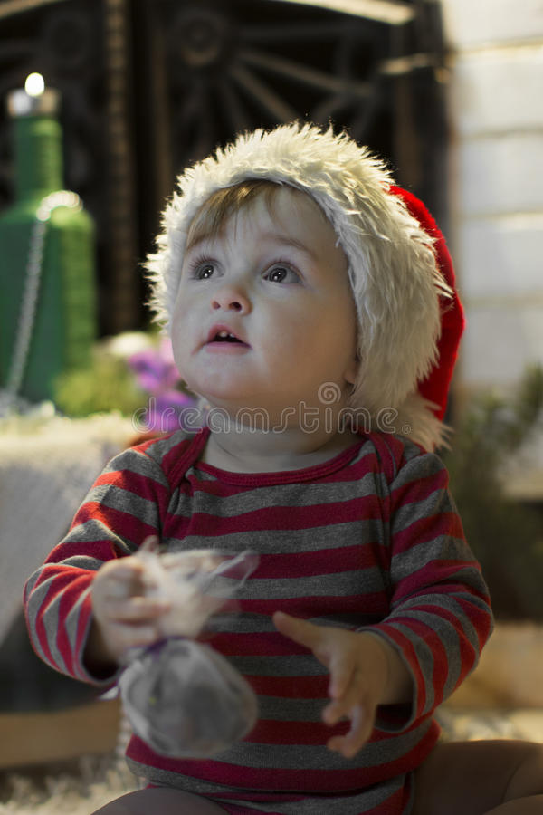 Baby in Santa hat with a gift curiously looking up royalty free stock images