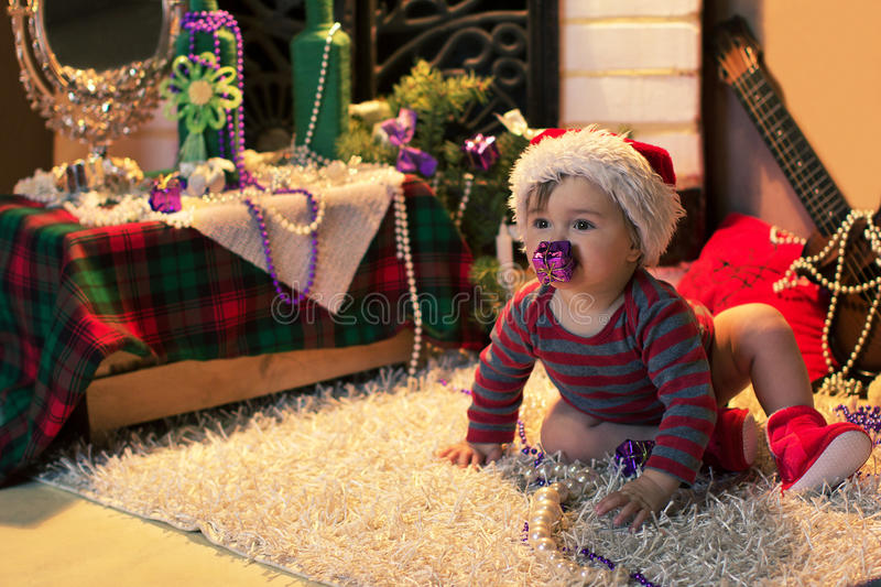 Baby in Santa hat with a gift in her mouth royalty free stock photo