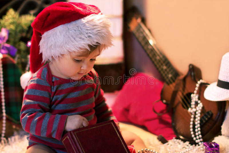 Baby in Santa hat keep a book royalty free stock image