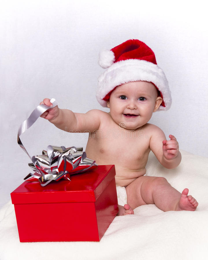 Baby in Santa Hat Playing with Christmas Gift royalty free stock photo