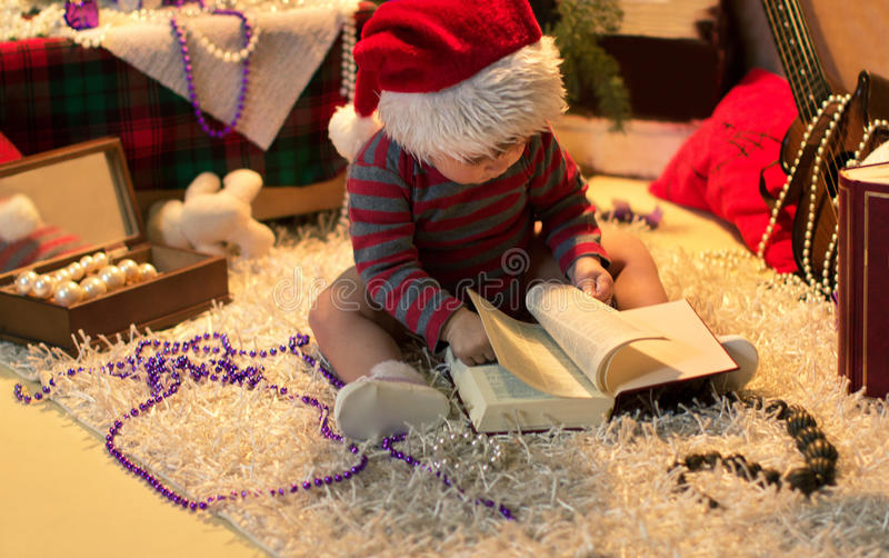 Baby in Santa hat read a book stock images
