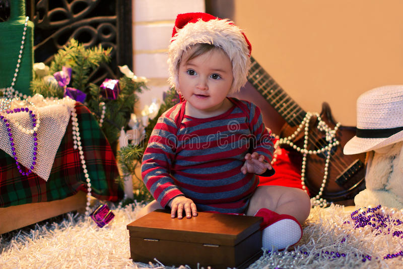 Baby in Santa hat sits on the carpet and openning a box. Funny baby in Santa hat sits on the carpet and openning a box near christmas tree royalty free stock images