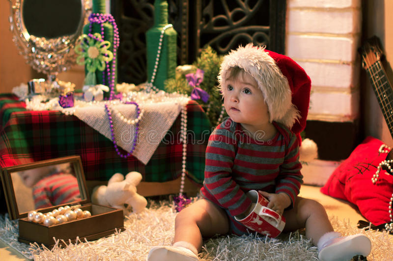Baby in Santa hat sitting on the carpet with a cap. Funny baby in Santa hat sitting on the carpet with a cap in her hands royalty free stock photos