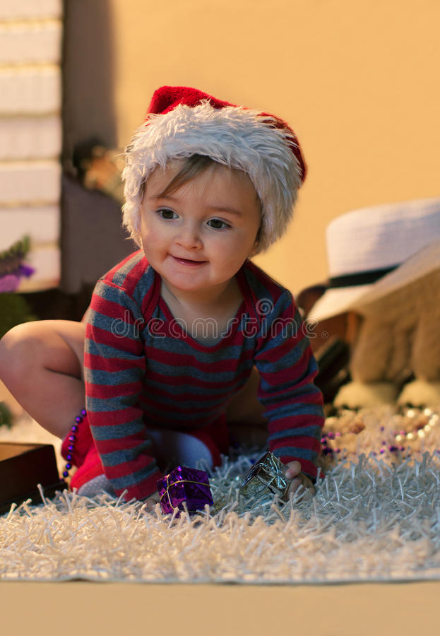 Baby in Santa hat with a small gifts stock photography
