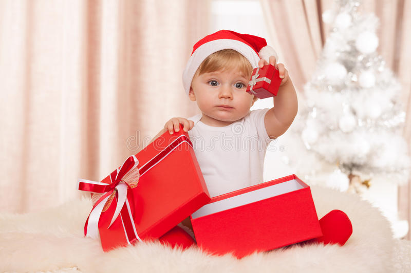 Baby santa holds a big red gift box stock photo