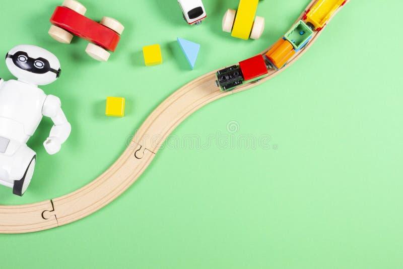 Baby scherzt Spielwarenhintergrund mit hölzernem Zug, Spielzeugroboter, Autos, bunten Blöcken und Ziegelsteinen auf grünem Hinter stockbilder
