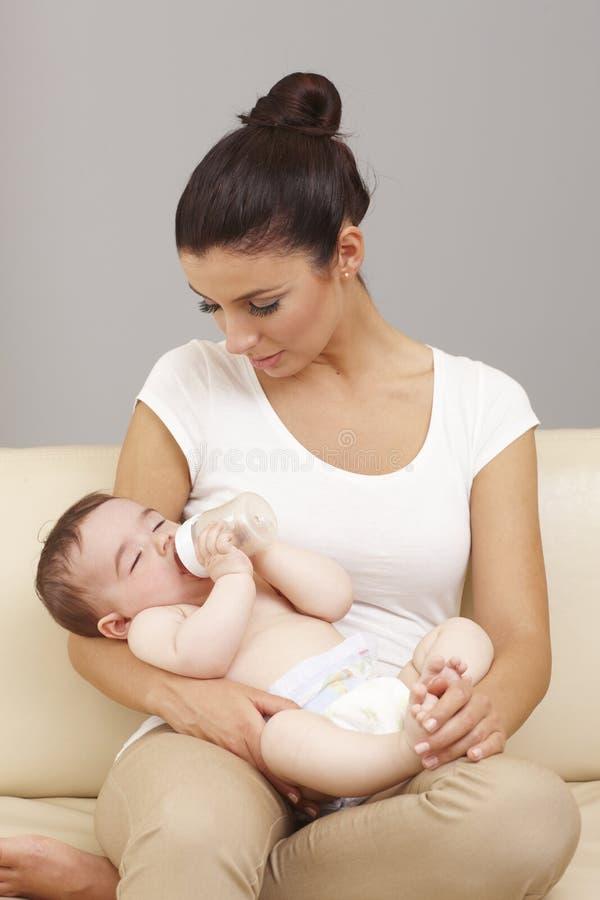 Baby schlief in Mutter ` s Arme ein lizenzfreie stockfotos