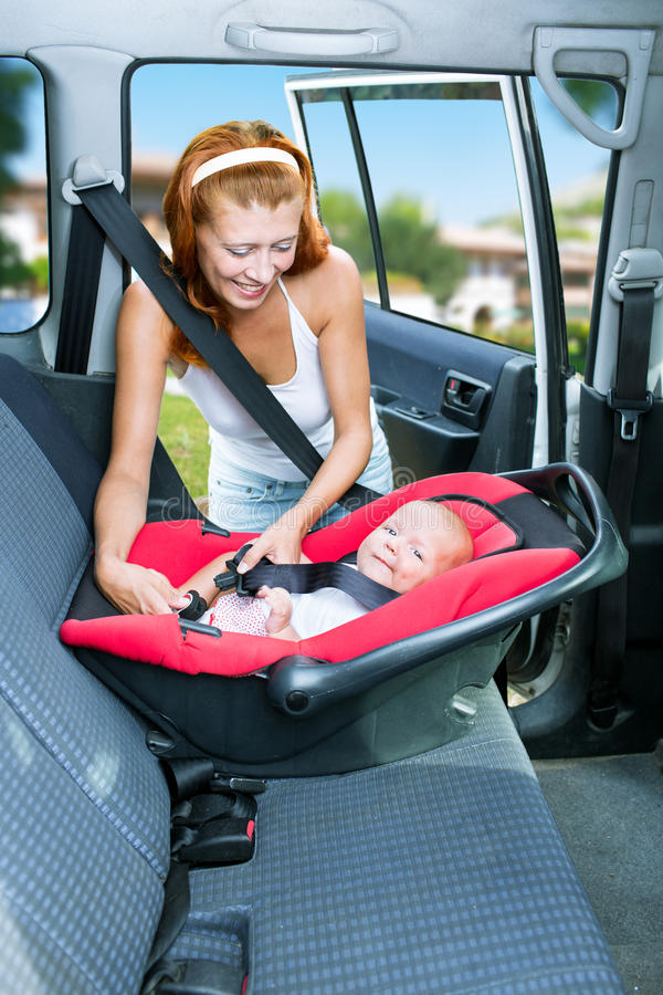 Baby seats in the car seat. Woman baby seats in the car seat royalty free stock photography