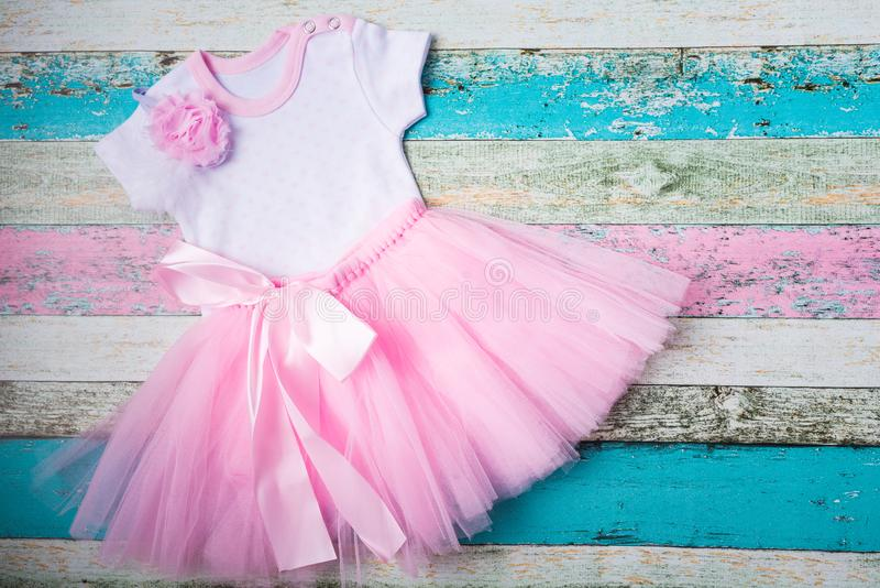 Baby set - pink tulle skirt, white bodysuit of hearts and a beautiful pink headband over pastel wooden background. Top stock photo
