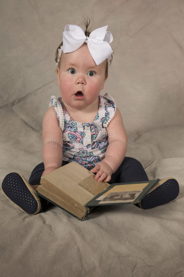 Baby shocked book. A baby girl sitting with a shocked expression, not sure what to think when she saw this book royalty free stock images