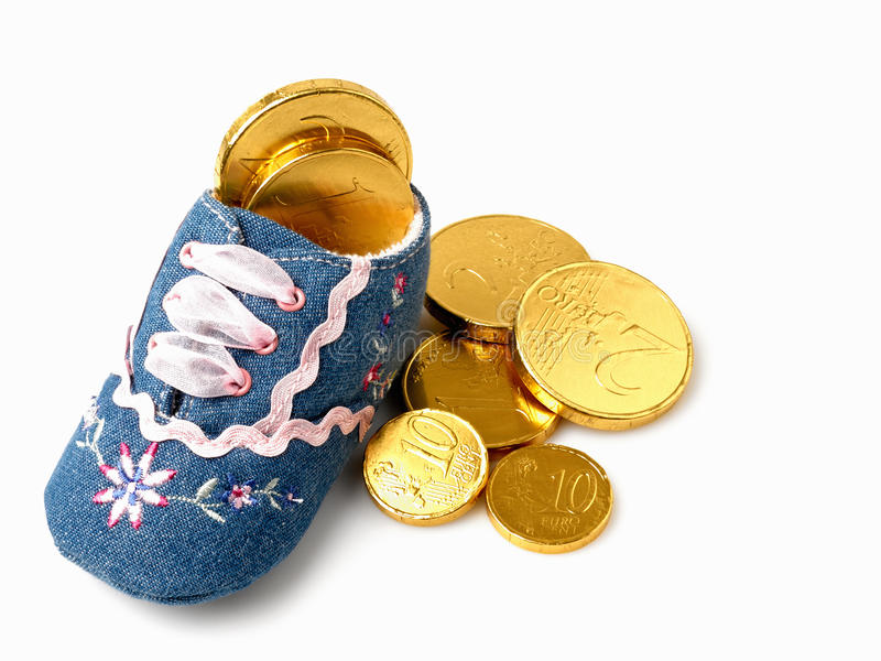 Baby shoe. Filled with fake golden coins royalty free stock images