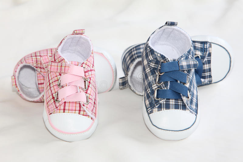 Baby Shoes. Two pair of Small baby shoes on soft silk royalty free stock images