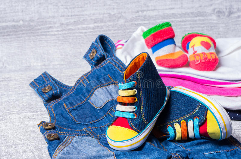 Baby shoes for babies and a set of clothes. In the background stock images