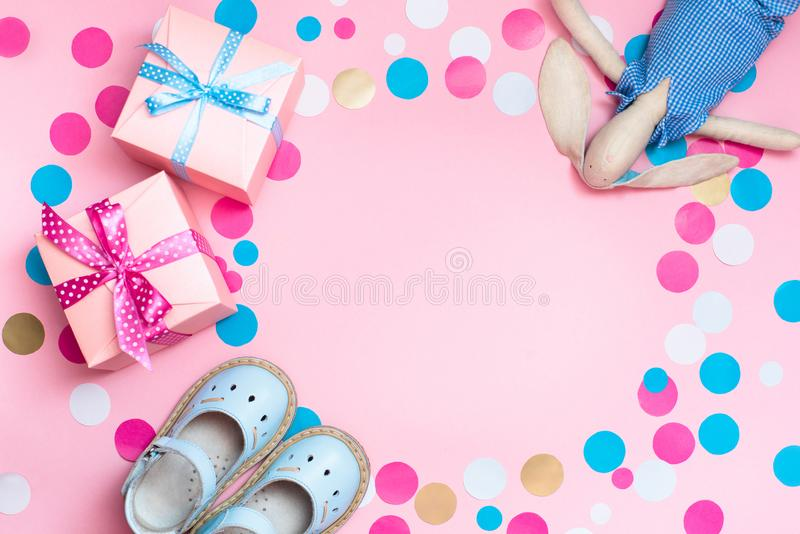 Baby shoes, gift boxes and confetti, on the pink background. stock photos