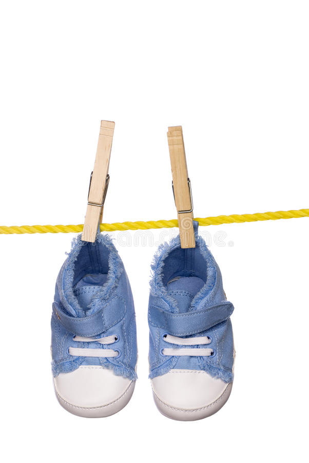 Baby shoes hanging on a clothesline stock images