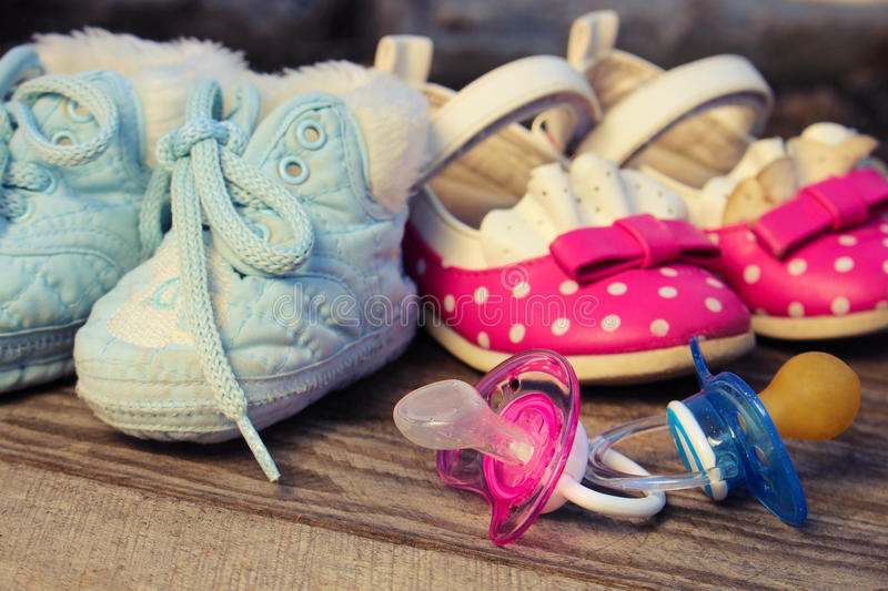 Baby shoes and pacifiers pink and blue on the old wooden background. royalty free stock image