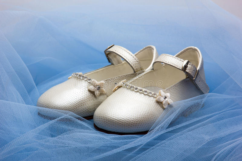 Baby shoes. Pair of baby shoes on a blue veil royalty free stock photo