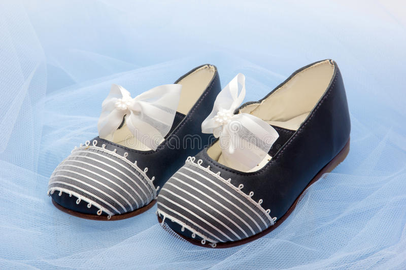 Baby shoes. Pair of baby shoes on a blue veil royalty free stock image