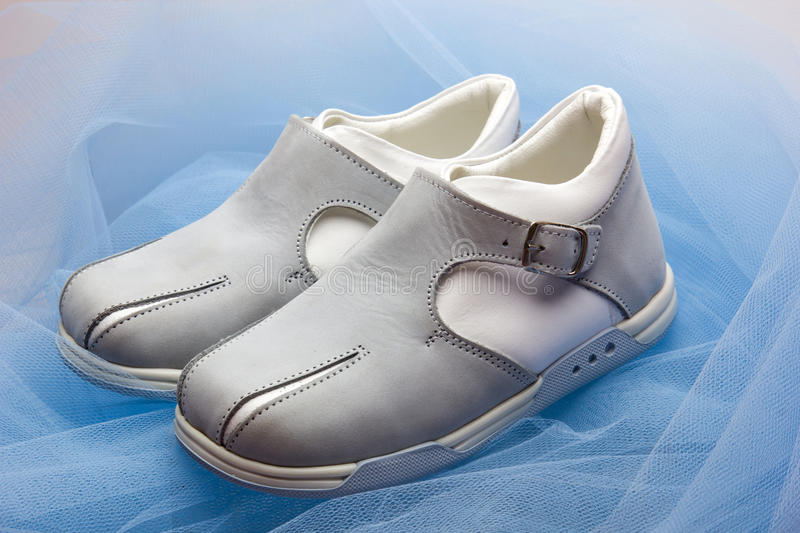 Baby shoes. Pair of baby shoes on a blue veil stock photography