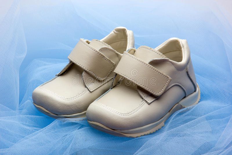 Baby shoes. Pair of baby shoes on a blue veil stock photo