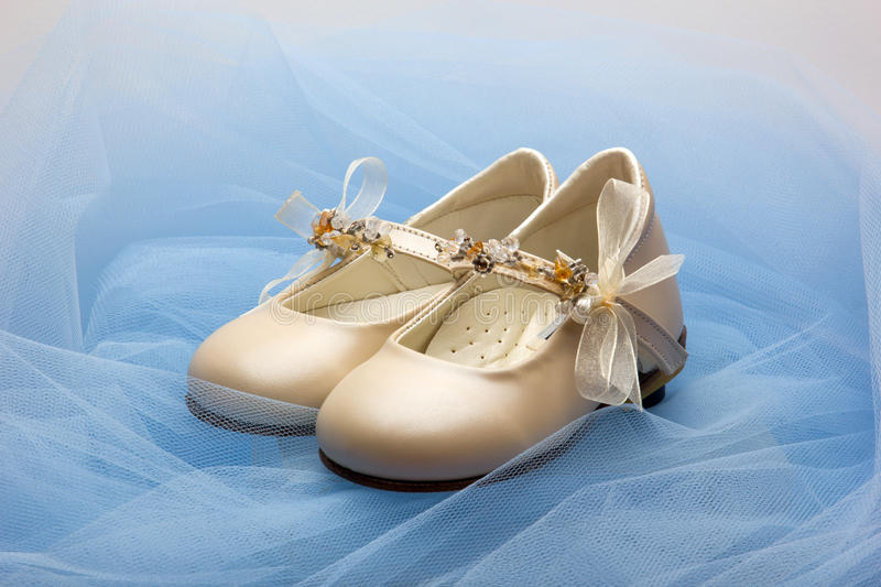 Baby shoes. Pair of baby shoes on a blue veil royalty free stock images