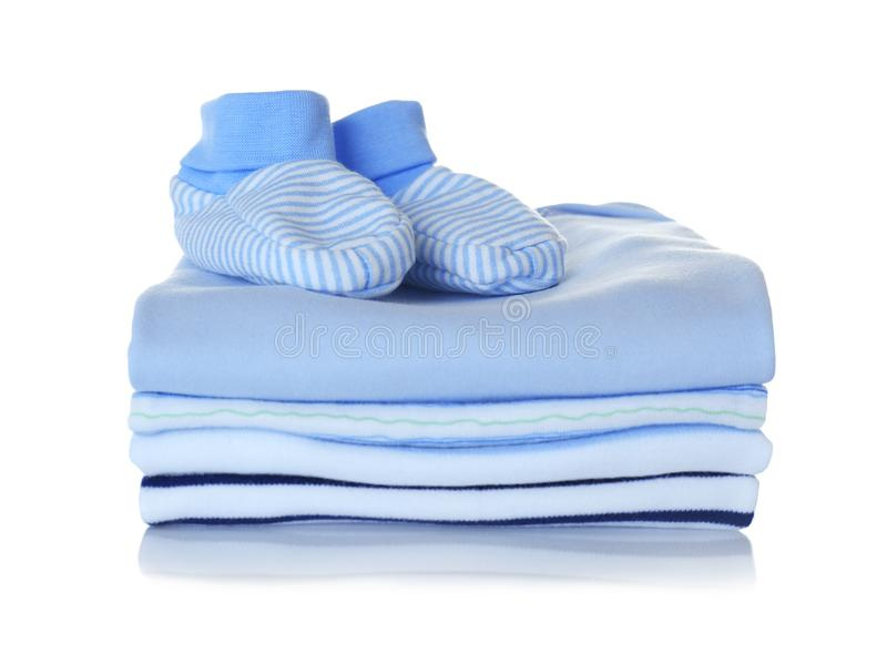 Baby shoes and pile of clothes. On white background royalty free stock photography