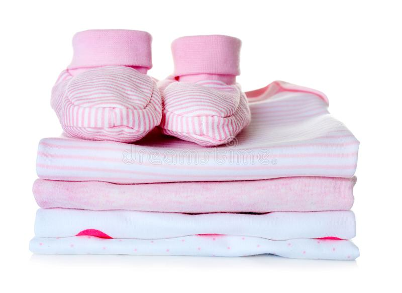 Baby shoes and pile of clothes. On white background royalty free stock photos