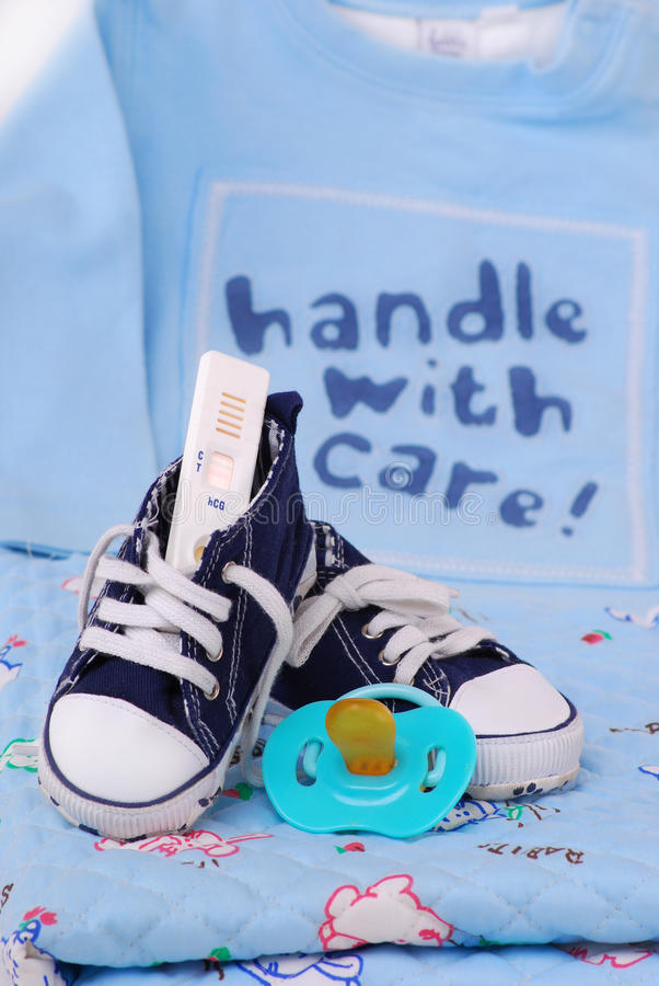 Baby shoes and pregnancy test stock image