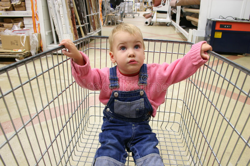 Baby in shop carriage. Baby sit in shop carriage stock photos