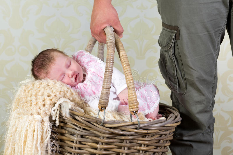 Baby shopping. Hands of a father carrying a wicker shopping basket with his 11 days old newborn baby girl royalty free stock photography
