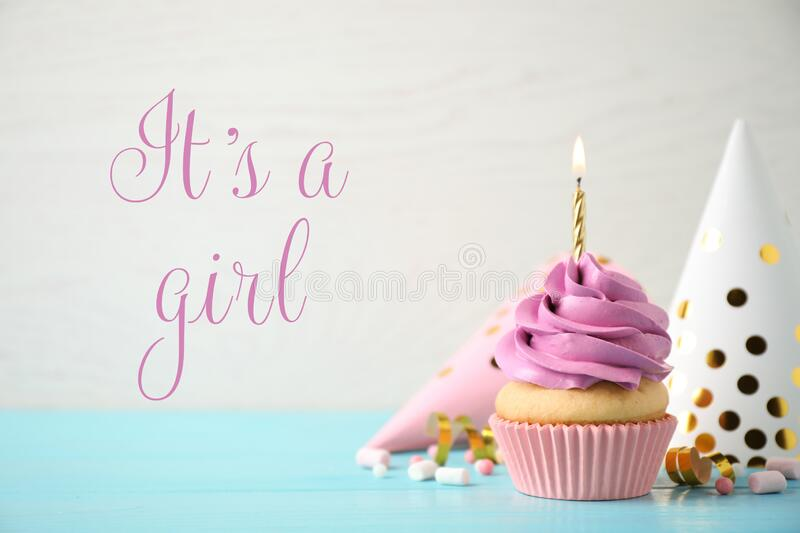 Baby shower cupcake with candle for girl on background. Baby shower cupcake with candle for girl on light background stock image