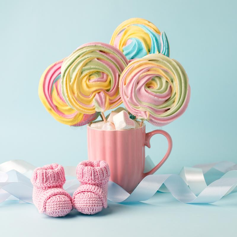 Baby shower decoration - it is a girl. Rainbow sweetness and knitted pink booties socks on blue background. First birthday, royalty free stock images