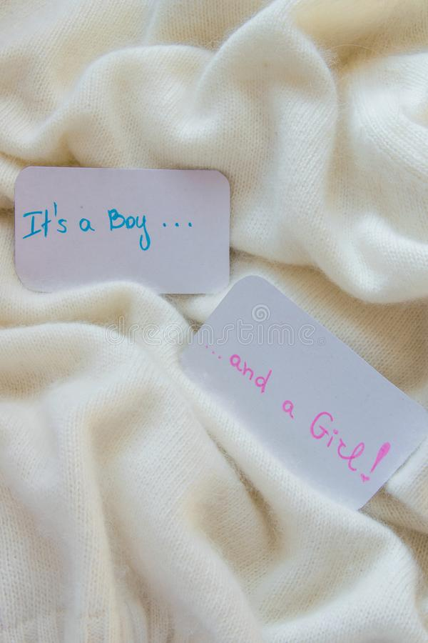 Baby shower `It`s a boy...and a girl`, announcement card on cozy warm white blanket with space for text stock photo