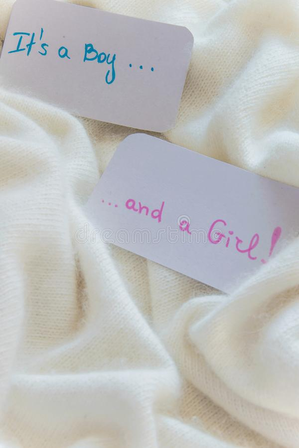 Baby shower `It`s a boy...and a girl`, announcement card on cozy warm white blanket with space for text. Twins arrivals stock photo