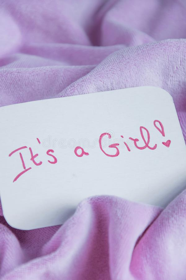 Baby shower `It`s a girl`, celebration card on cozy pink blanket with space for text royalty free stock photography